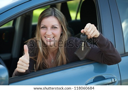 A happy driver leaning out of the window and showing the car key - stock photo