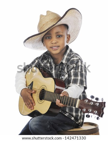 A happy elementary cowboy strumming a guitar while sitting on an old barrel.  On a white background. - stock photo