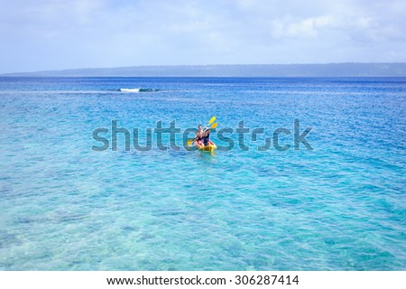 A happy family: dad and his children- a boy and a girl kayaking in the blue waters of the ocean - stock photo