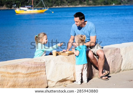 A happy family- dad or father and his young children sitting on the rock border and enjoying some food on a sunny summer day with the sea and boats in the background - stock photo