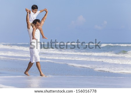 A happy family, father parent & boy son child, playing and having fun in the waves of a sunny beach - stock photo