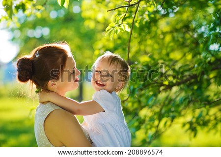 A happy family in the green garden in a sunny spring day: a beautiful young slender mother holding her little laughing daughter in her arms  - stock photo