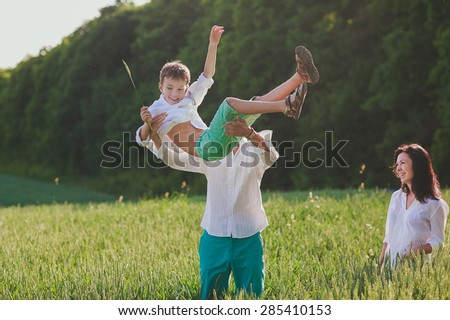 a happy family is having fun, a father is lifting his son into the air