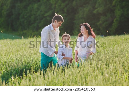 a happy family is standing in the green field of wheat