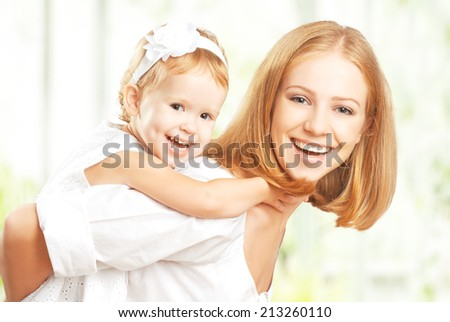 A happy family: mother and baby daughter hugging and laughing - stock photo