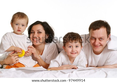 A happy family of four people lying on the bed