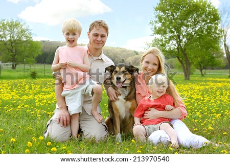 A happy family of four people, mother, father, young child and toddler are sitting in a meadow of Dandelion flowers with their German Shepherd mix dog, on a beautiful Spring day. - stock photo