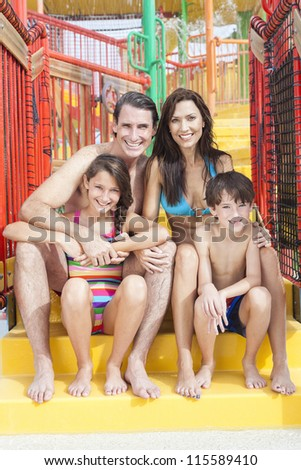 A happy family of mother, father and children, son and daughter, having fun on vacation at a water park - stock photo