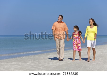 A happy family of mother, father and daughter, holding hands and walking in the sand of a sunny beach