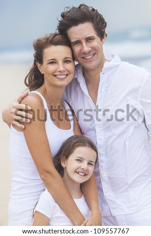 A happy family of mother, father and one child, a daughter, embracing and having fun on a sunny tropical beach