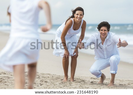 A happy family of mother, father and one child, a daughter, running and having fun in the sand of a sunny tropical beach - stock photo