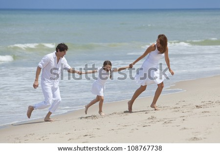 A happy family of mother, father and one child, a daughter, running holding hands and having fun in the sand of a sunny tropical beach