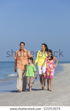 A happy family of mother, father and two children, son and daughter, walking holding hands and having fun in the sand of a deserted sunny beach - stock photo