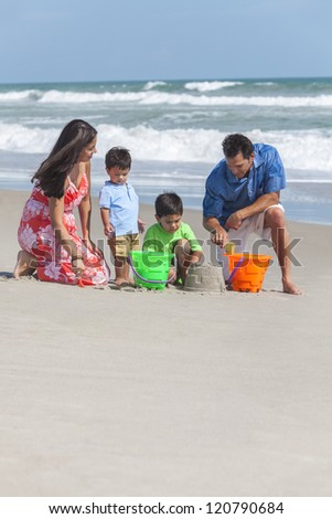 A happy family of mother, father and two children, two boy sons, playing and having fun making sandcastles on a sunny beach - stock photo