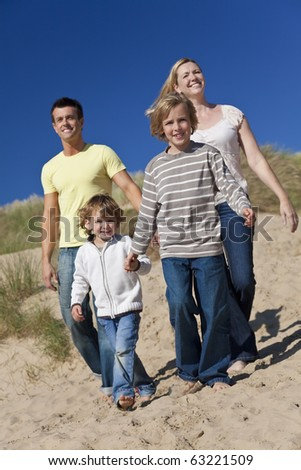 A happy family of mother, father and two sons, walking holding hands and having fun in the sand dunes of a sunny beach