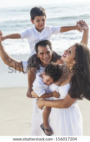 A happy family of mother, father parents & two boy son children, playng and having fun in the waves of a sunny beach