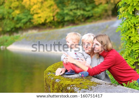 A happy family of three generations, mother, daughter, grandmother and little baby granddaughter, are standing together on the bridge of the river with the colorful trees around