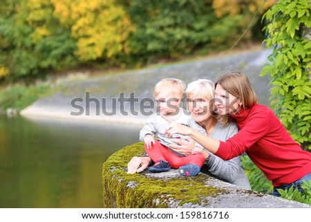 A happy family of three generations, mother, grandmother and little baby granddaughter, are standing together on the bridge of the river with the colorful trees around