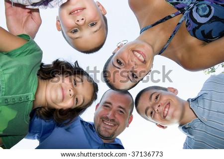 A happy family posing in a group huddle formation. - stock photo