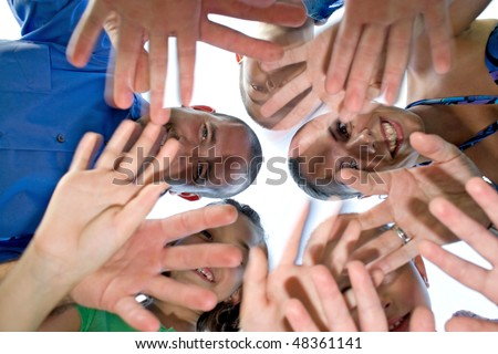 A happy family posing in a group huddle formation and waving at the camera.  Intentional motion blur of the hands.