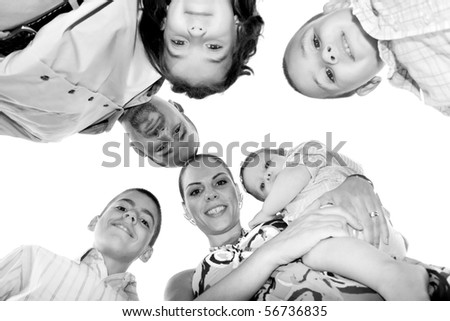 A happy family posing in a group huddle formation with a unique perspective. - stock photo