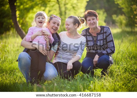 A happy family sit in the grass with husky smilling - stock photo