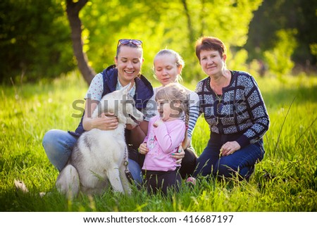 A happy family sit in the grass with husky smilling