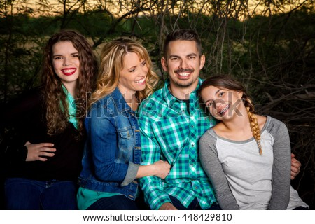 A happy family sits in a row, smiling for the picture.  The mom looks admiringly at her youngest daughter.  Parents with two teen girls. - stock photo