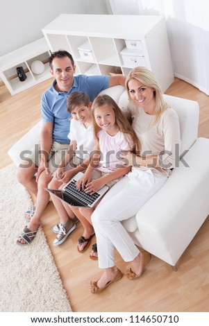 A Happy Family With Two Children Sitting On A Sofa Using Laptop At Home