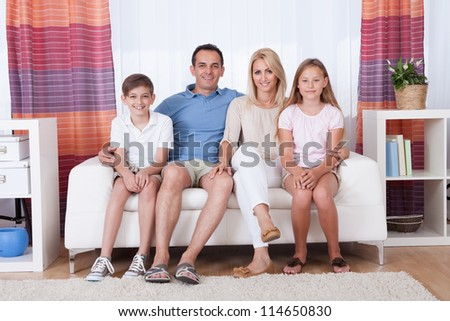 A Happy Family With Two Children Sitting On Sofa At Home - stock photo