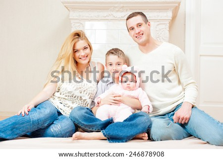 A happy family with two children sitting on the floor at home - stock photo
