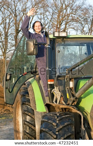 A happy farm hand standing in the door opening of a big tractor, waving at the camera - stock photo