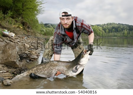 A happy fisherman presenting his fishing trophy caught in a Polish lake - catfish (Silurus glanis)