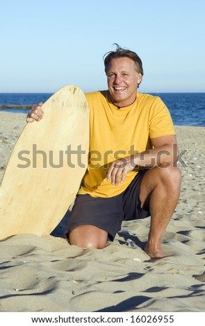 A happy forties man having fun on the beach with his surfboard/skim-board. - stock photo