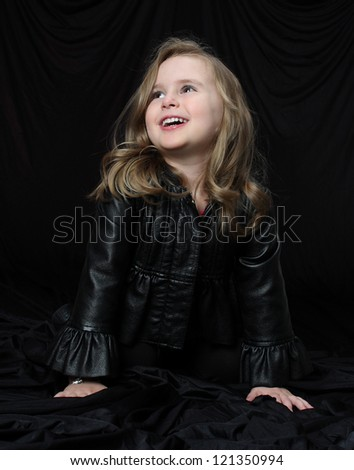 A happy girl in black leather coat laughs and chuckles