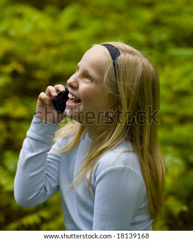 A happy girl on a cell phone outdoors - stock photo