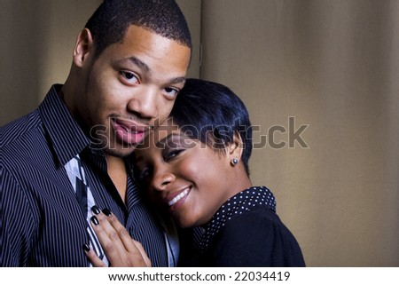 A happy girl places her head and hand on her lover's chest with his tie undone.