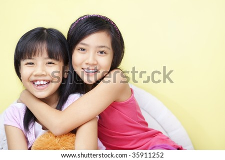 A happy girl with her little sister in bedroom - stock photo