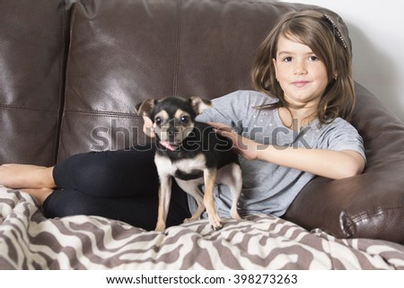 A Happy girl with his dog on sofa