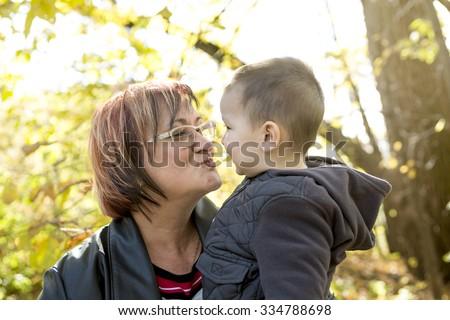 A happy grandma with grandson outdoor in autumn season - stock photo