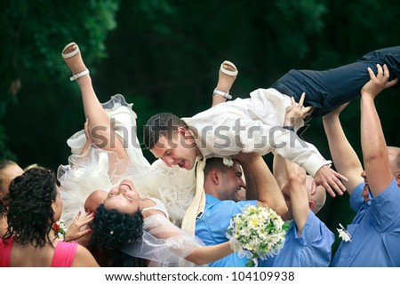 A happy groom and bride  tossed into air by a group of friends - stock photo