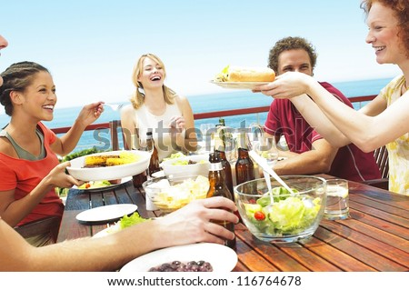 A happy group of teenage friends sitting at a table at the seaside drinking beer and eating their lunch - stock photo