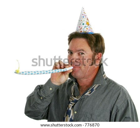 A happy guy at a new years eve party blowing a noisemaker and wearing a party hat.