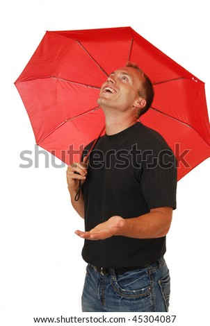 A happy handsome young man under an umbrella with his hand out - stock photo