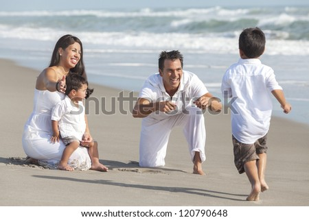 A happy Hispanic family of mother, father and two children, boy sons, playing and having fun in the sand of a sunny beach - stock photo