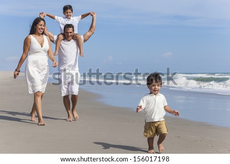 A happy hispanic family of mother, father parents & two boy son children, playng and having fun in the waves of a sunny beach - stock photo