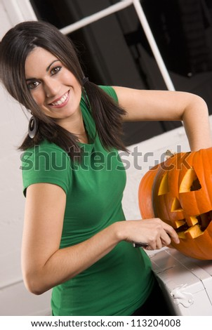 A happy house wife carves the pumpkin for Halloween vertical background