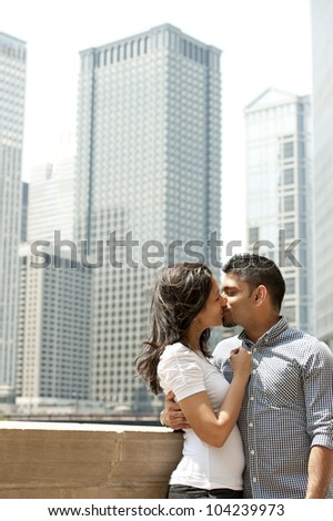 A happy Indian couple with a Chicago skyline in the background.