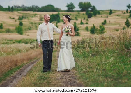 a happy just married couple is walking down a field path