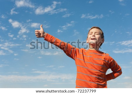 A happy kid is holding his thumb up and singing in front of the blue sky - stock photo